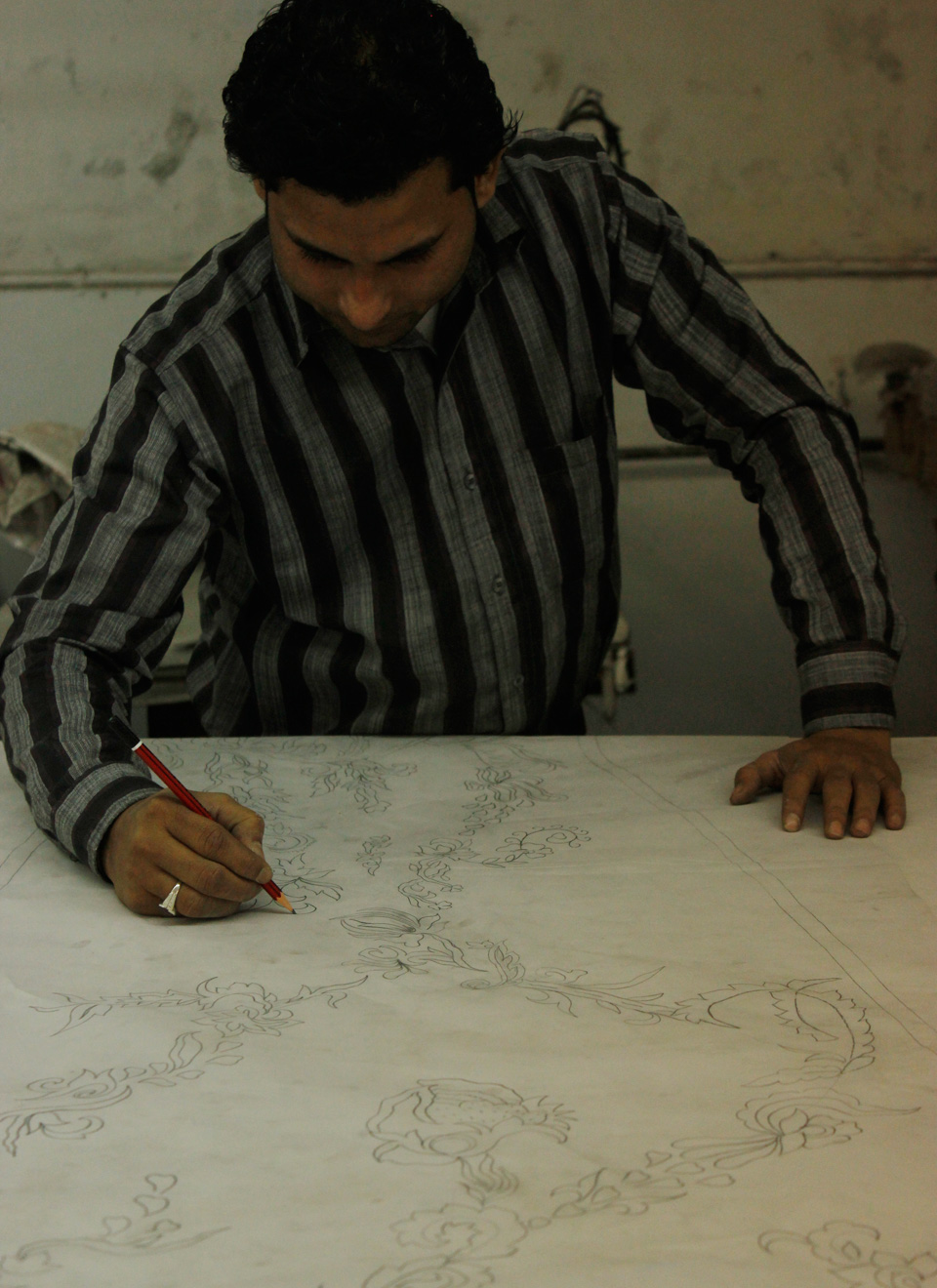 Our head designer traces the images to prepare them for hand embroidery.