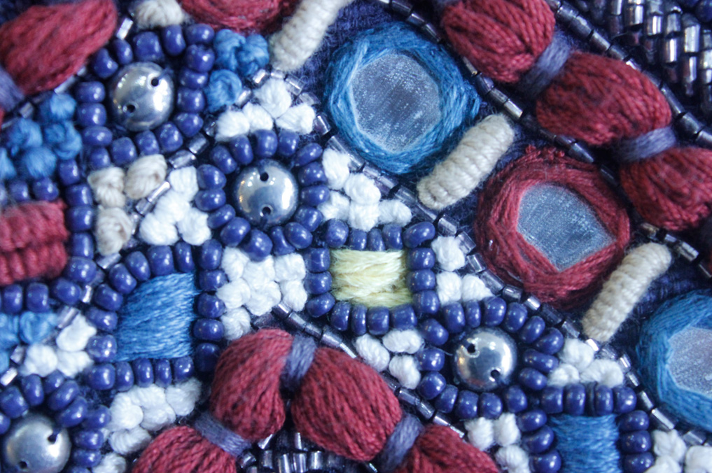 French knots hand embroidered with mirrors and beads in thick cotton thread.